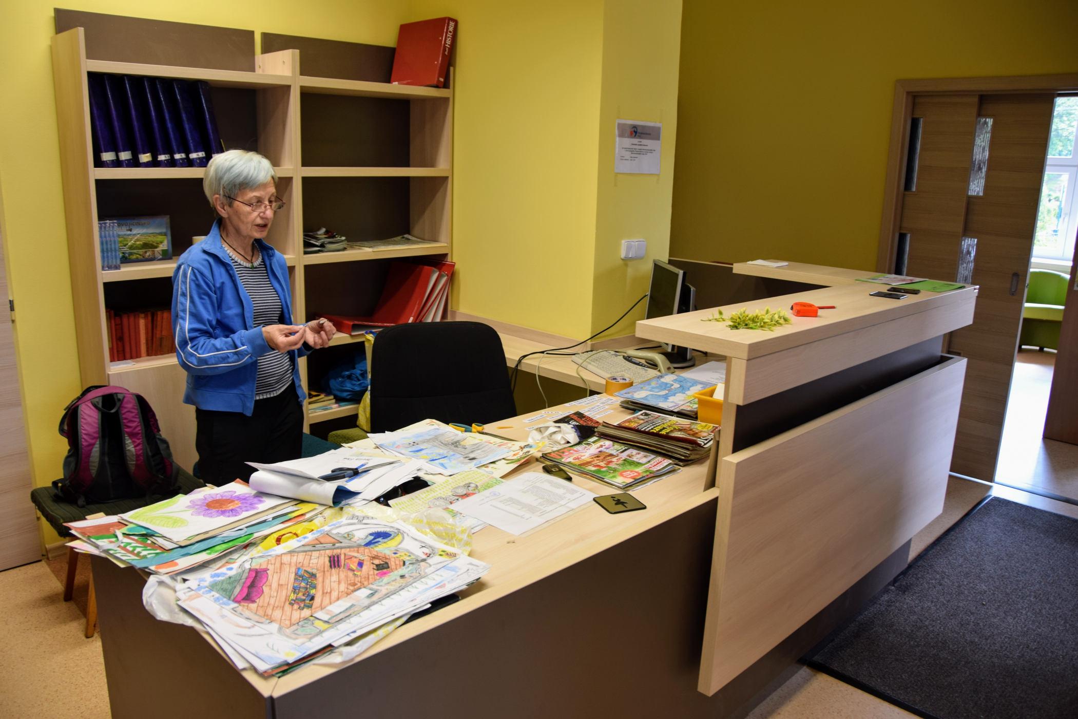Knihovnice Dana Sulovská za pultem nové knihovny