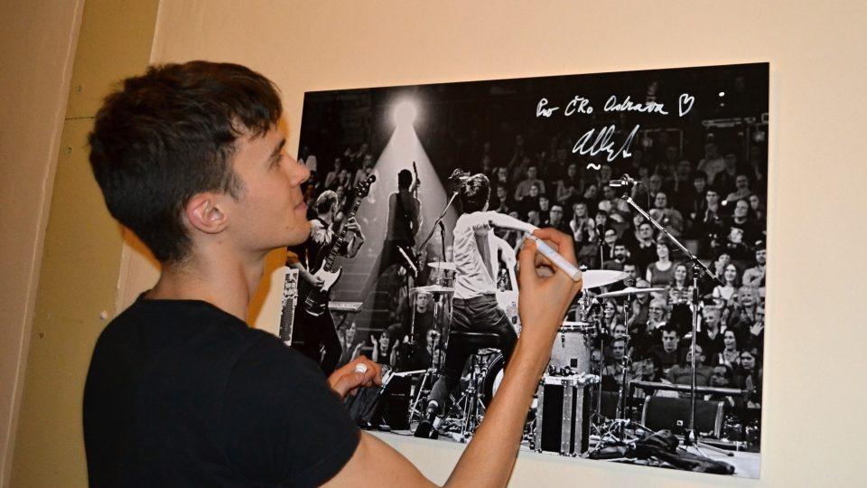 Albert Černý podepisuje fotografii Martina Straky, na které je zachycen ještě s kapelou Charlie Straight