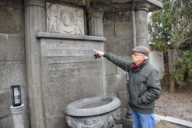 Pavel Wessely ukazuje na nápisy na opravené hrobce rodiny Weissů