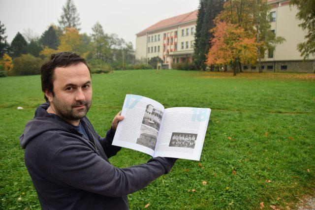 Ondřej Šalek ukazuje fotky v knize 70 let města Kopřivnice. Vlevo dole původní snímek Základní školy Pionýrská, nyní Emila Zátopka (v pozadí)