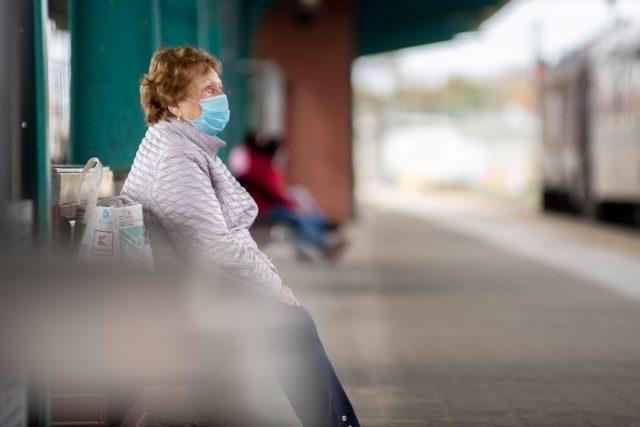 Starší žena čeká na nástupišti na vlak