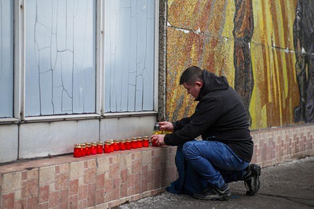 Lidé před budovou dolu ČSM zapalují svíčky